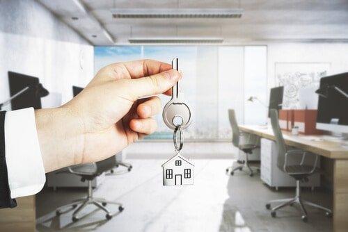 איש עסקים מחזיק מפתח להשכרת משרד אחרי קבלת טיפים מנצחים מטאוור לנד על השכרת משרדים